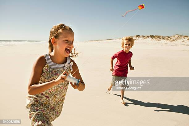 Boy (6-7) and girl (8-9) flying kite on sandy beach