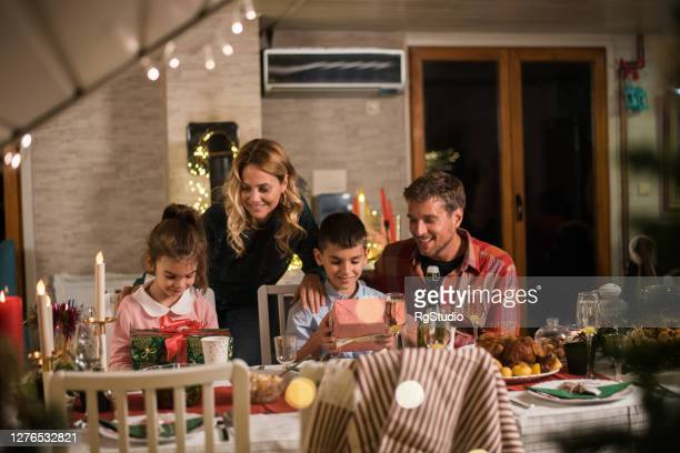 boy and girl getting christmas presents from parents - simple living stock pictures, royalty-free photos & images
