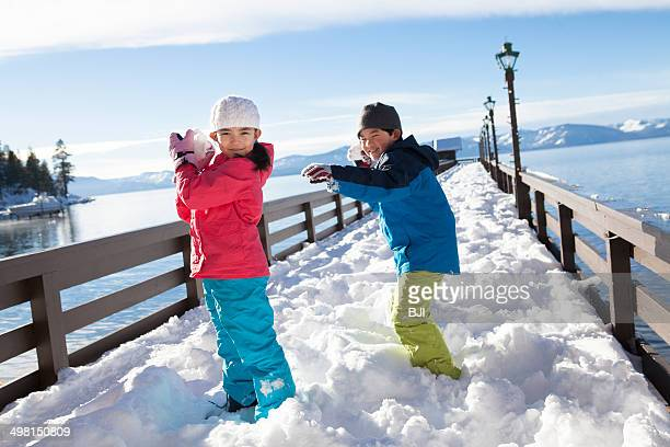 Boy and girl having a snowball fight