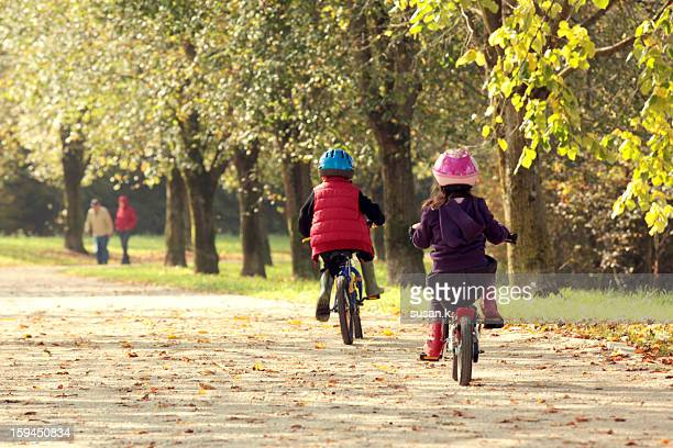 Boy and girl having bike race in the park.