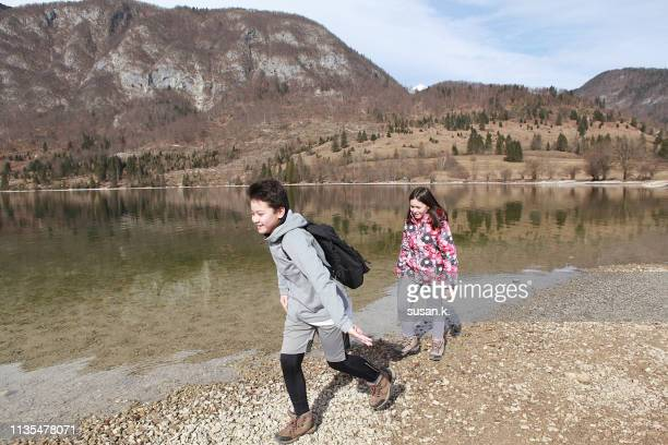 boy and girl having fun, enjoying nature by the lake. - 10歳から11歳 ストックフォトと画像