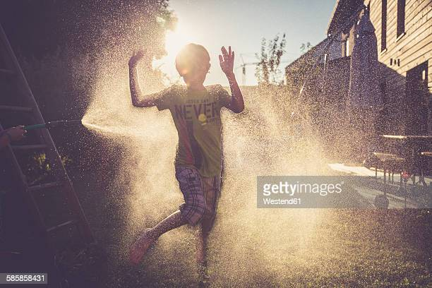 Boy and girl having fun with splashing water in the garden