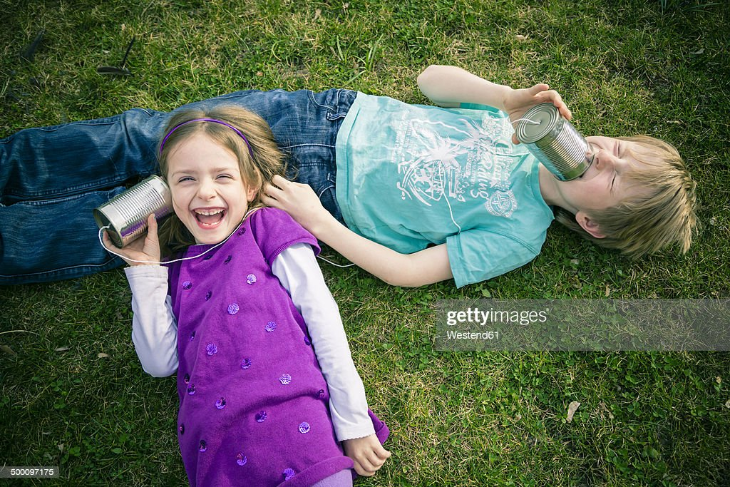 Boy and girl having fun with tin can phone : Stock Photo