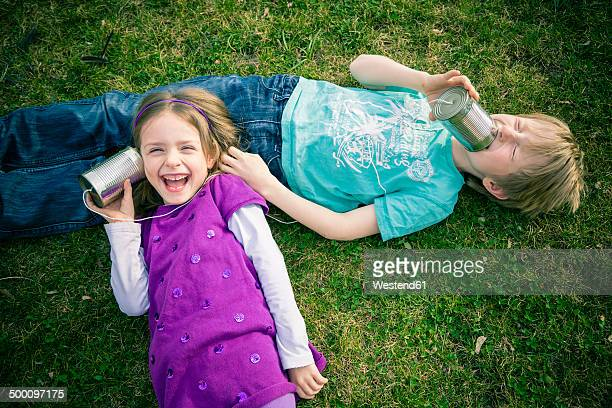Boy and girl having fun with tin can phone
