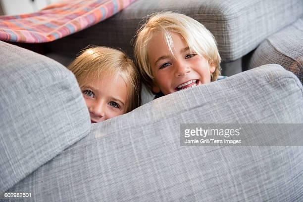 Boy (4-5) and girl (6-7) hiding behind pillows