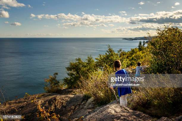 boy and girl hiking across rocks by a lake, lake superior provincial park, united states - lake superior provincial park stock pictures, royalty-free photos & images