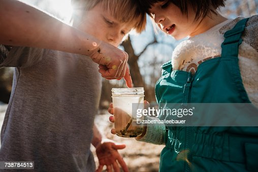Boy and girl holding a jar with water bugs