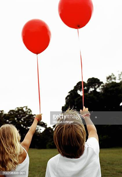 boy and girl (9-12) holding balloons in field, rear view - blasius erlinger stock pictures, royalty-free photos & images