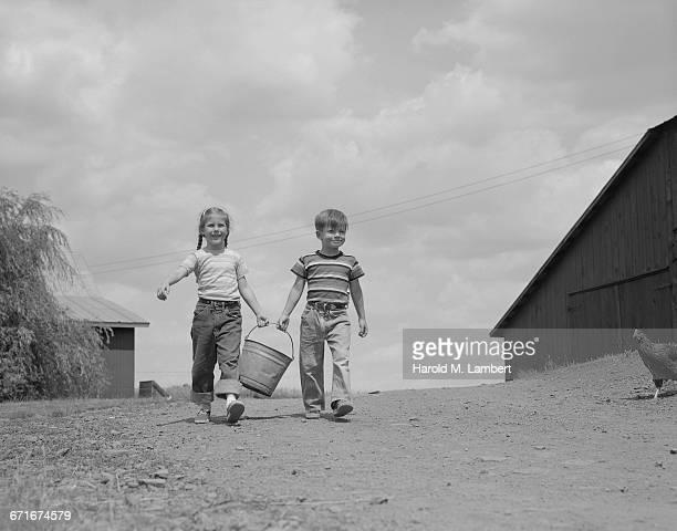 boy and girl holding bucket and walking - {{ contactusnotification.cta }} stockfoto's en -beelden
