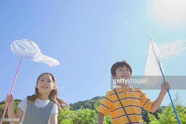 Boy and Girl Holding Butterfly Net