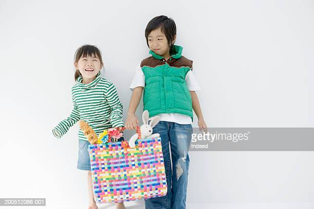 boy (4-6) and girl (3-5) holding colorful bag full of toys, smiling - 兄弟 ストックフォトと画像
