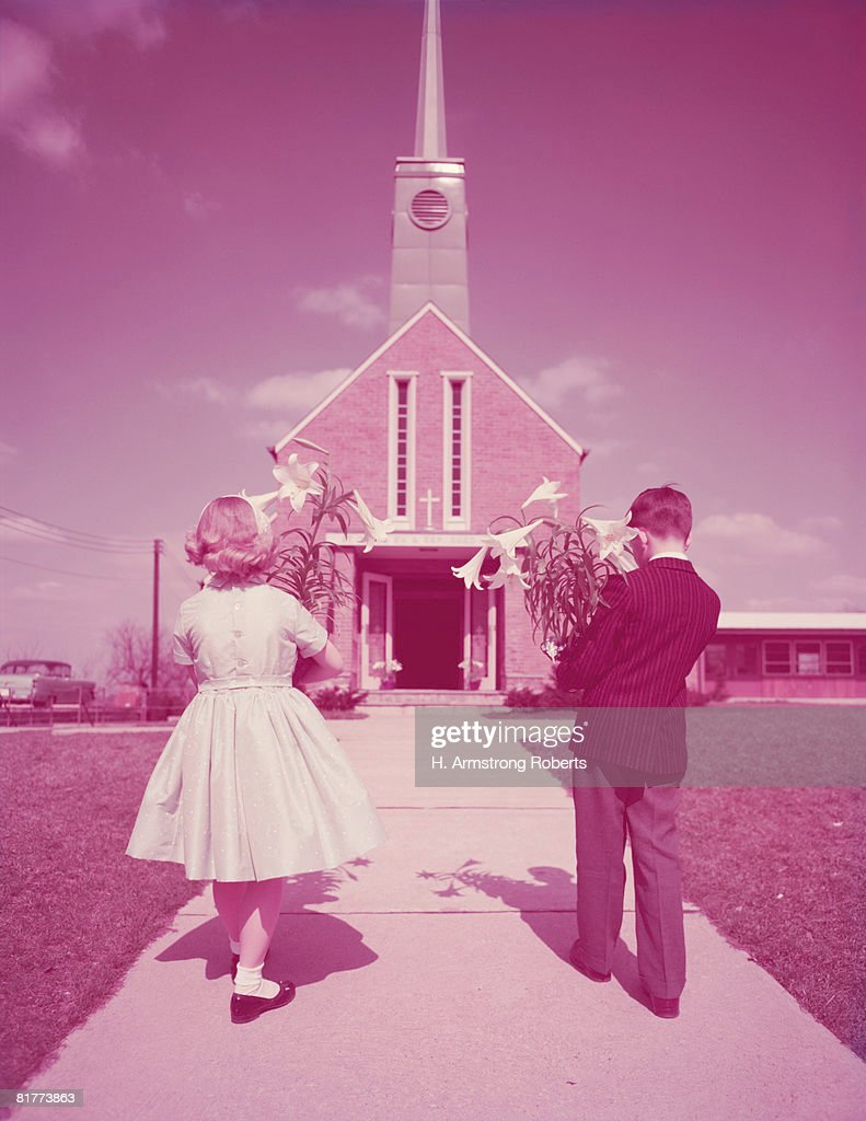 boy and girl holding easter lilies walking to church ストックフォト