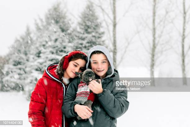 boy and girl holding french bulldog puppy wearing Christmas sweater outside during a snowfall