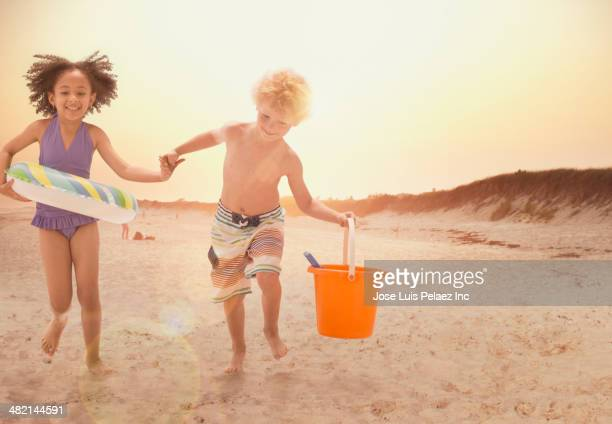 Boy and girl holding hands and running on beach at sunset