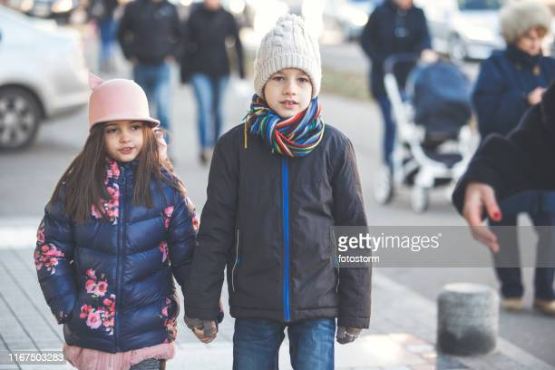 Boy and girl holding hands while walking in the city