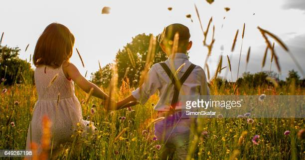 boy and girl holding hands while walking on field - flat cap stock pictures, royalty-free photos & images