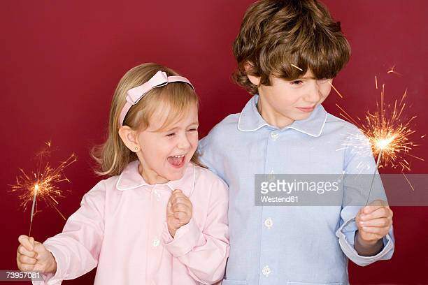 Boy (4-7) and girl (3-4) holding sparklers