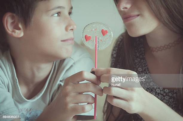 Boy and girl holding valentine day's lollipop