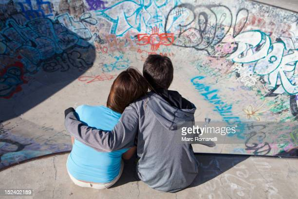 boy and girl hugging in skateboard park - arm around stock pictures, royalty-free photos & images