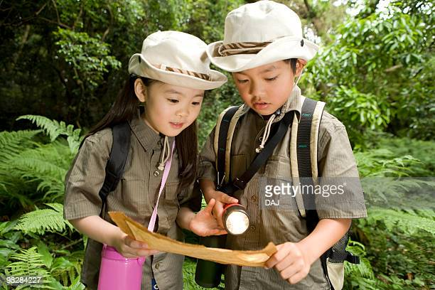 Boy and girl in a forest looking at map