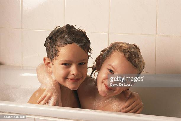 Boy and girl (6-9) in bathtub with arms around, smiling, portrait