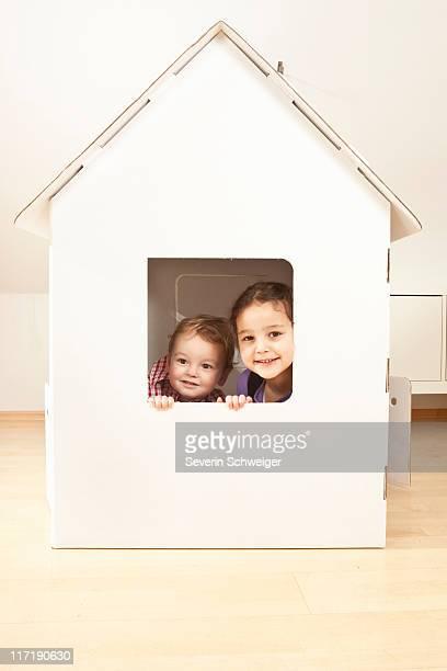 Boy and girl in cardgoard house