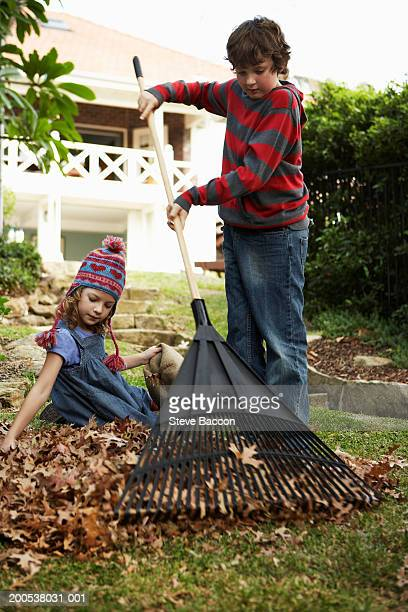 Boy and girl (6-10) in garden raking leaves