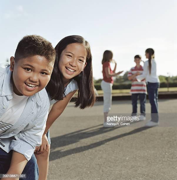 Boy and girl (9-11) in schoolyard, portrait