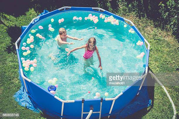 Boy and girl in swimming pool surrounded by balloons