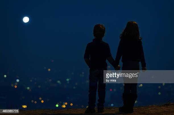 Boy and girl in the night over the city, full moon