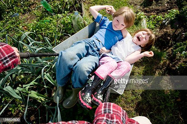 Boy and girl in wheelbarrow, high angle