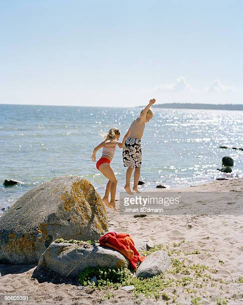 Boy and girl jumping from a stone on a beach Sweden.