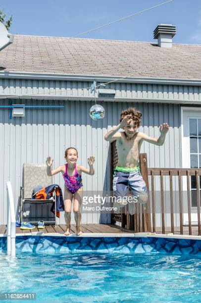 boy and girl jumping in domestic pool - kids pool games stock pictures, royalty-free photos & images