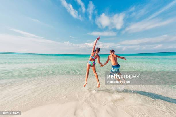 boy and girl jumping in the surf of the gulf of mexico - florida beach stock pictures, royalty-free photos & images