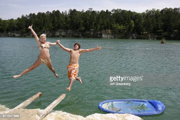 A boy and girl jumping into the water at St Stephens Historic Site