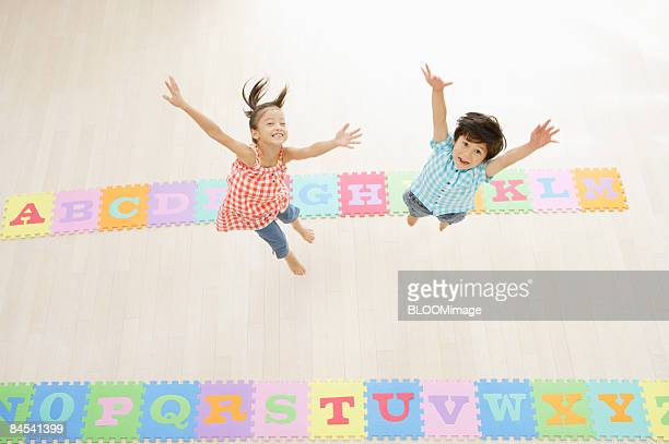 Boy and girl jumping, raising hands, view from above