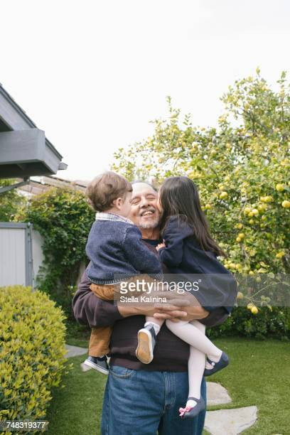 Boy and girl kissing grandfather