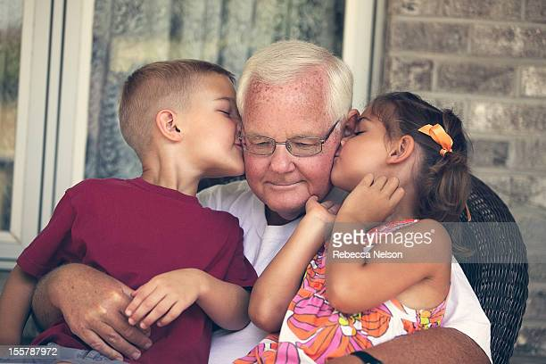boy and girl kissing their grandpa's cheeks