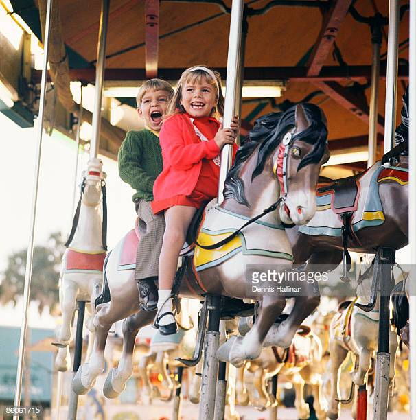 Boy and girl laughing riding carousel