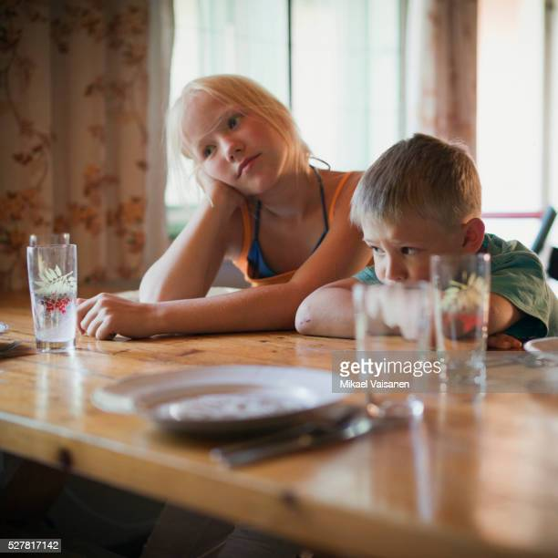 Boy and girl (3-9) leaning on table looking bored