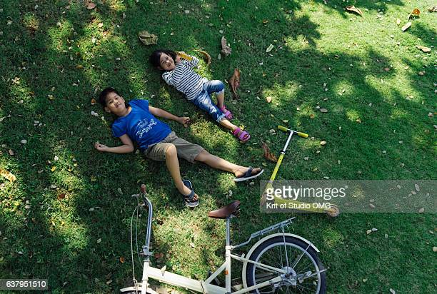 Boy and Girl lie on green lawn under tree shade