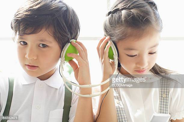 Boy and girl listening to music with mp3 player, sitting by window