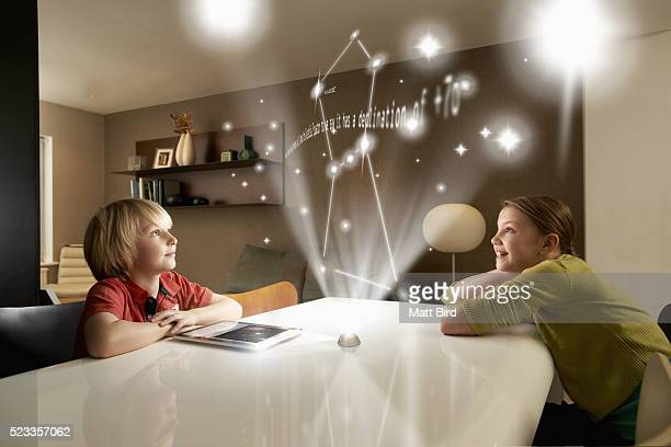 Boy and girl looking at astronomical projection on futuristic device