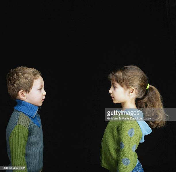 Boy and girl (3-6) looking at each other, side view