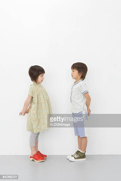Boy and girl looking at each other, side view