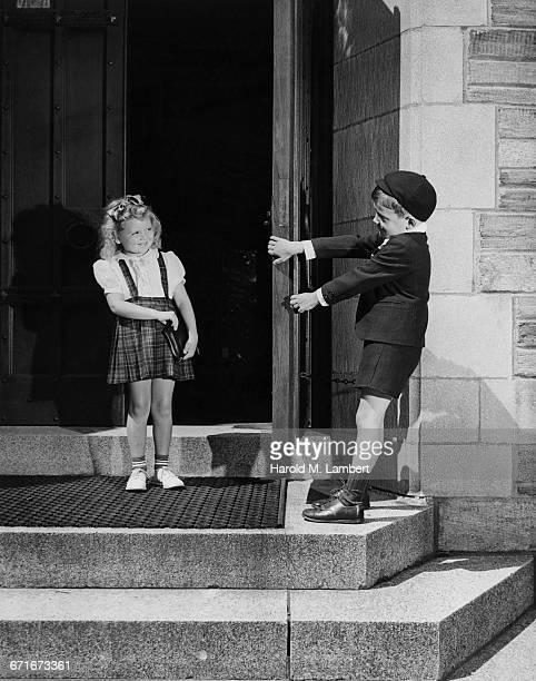 boy and girl looking at each other while playing on doorstep - {{ contactusnotification.cta }} stockfoto's en -beelden
