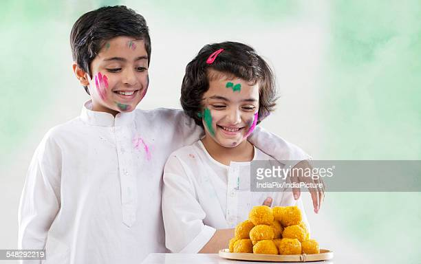 boy and girl looking at laddoos - mithai stock pictures, royalty-free photos & images