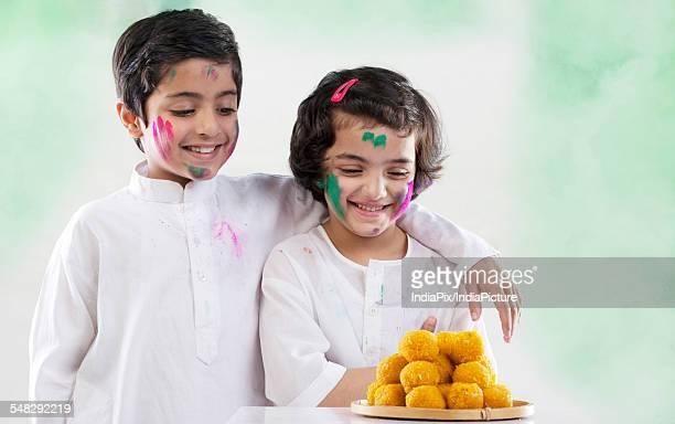 Boy and girl looking at laddoos