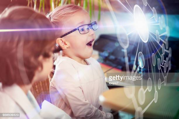 boy and girl looking at network hologram - nerd girl stock photos and pictures