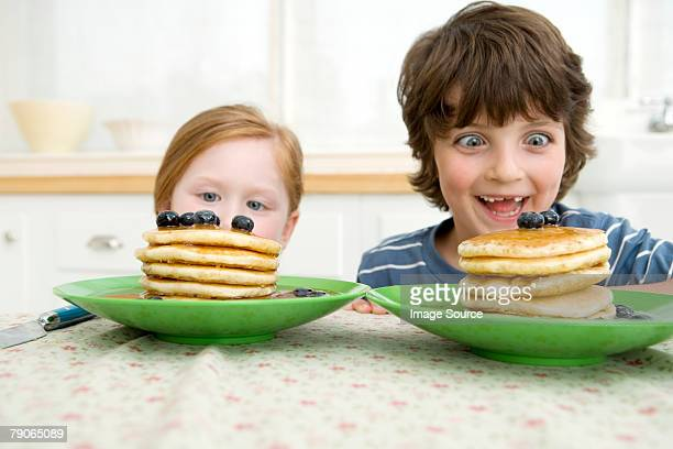 boy and girl looking at pancakes - pancake stock pictures, royalty-free photos & images